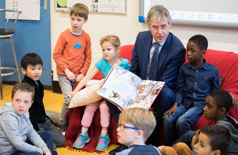 Minister Slob leest op basisschool het Kompas in Rotterdam voor aan kinderen uit groep drie. Beeld Martijn Beekman