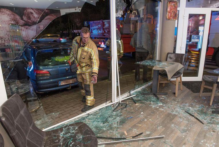 De auto bolde door dit raam de frituur binnen. De brandweer heeft hem weer uit de zaak gehaald.