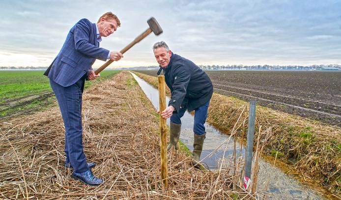 Burgemeester Marnix Bakermans slaat het eerste paaltje bij het inmeten van de percelen in de agro-proeftuin.