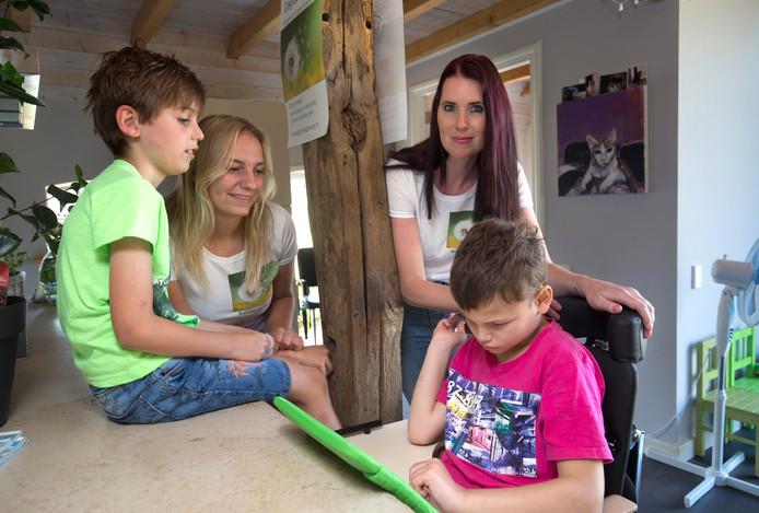 Mieke Grimm (rechts) met haar zoontje Emre (links), begeleidster Aniek Bloemendaal en Finn in de opvangboerderij voor complex zieke kinderen in Wichmond.