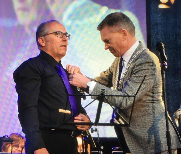 Burgemeester Peter Rehwinkel speldt de onderscheiding op bij Herman van Veen.