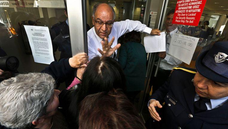 Een manager van de Laiki Bank probeert mensen te kalmeren die wachten tot de bank zijn deuren opent. Beeld reuters