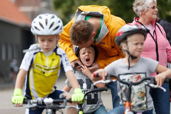 Voor het fietsen laat een rennertje nog even de helm goed opzetten door papa. Liefst niet te strak. Foto Marcel Otterspeer/Pix4Profs