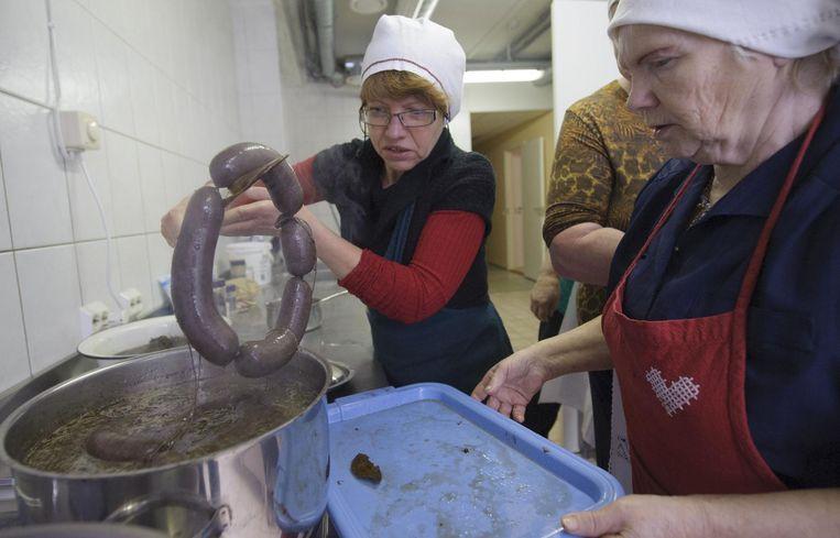 Vrouwen in Tallinn bereiden bloedworst voor kerst. Beeld AFP