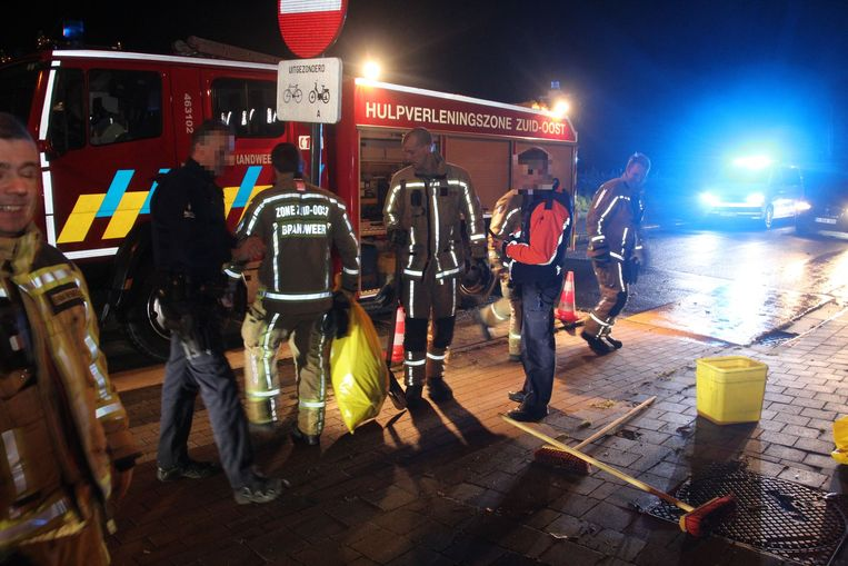 Nadat brokken en olie waren opgeruimd duwden brandweermannen het verkeersbord terug recht.