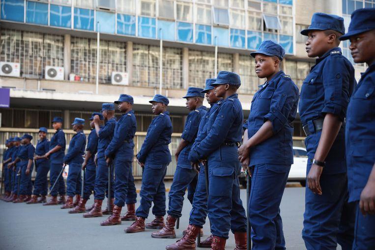 De situatie in de Zimbabwaanse hoofdstad Harare blijft gespannen, de politie staat paraat in een lege straat. Beeld Getty Images