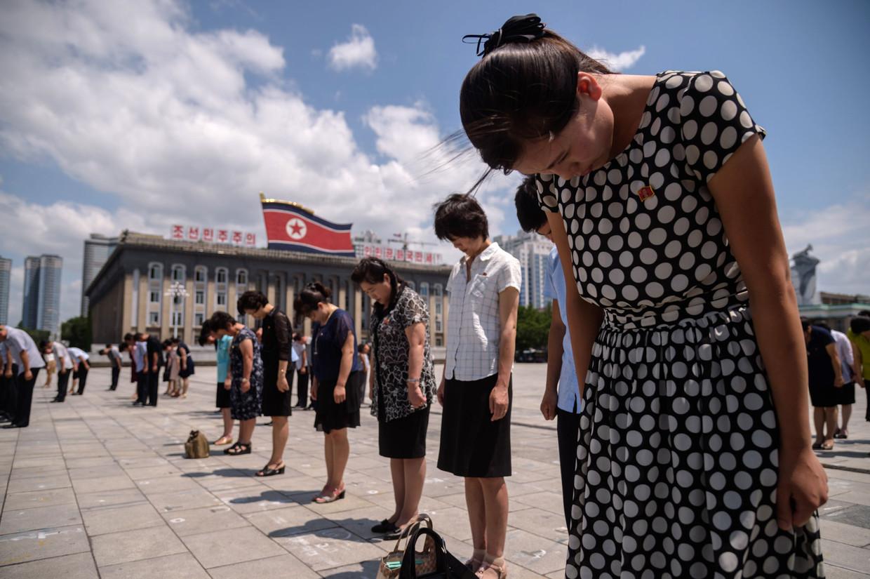 Noord-Koreanen buigen in de hoofdstad Pyongyang voor de portretten van de vroegere leiders Kim Il-sung en Kim Jong-il.