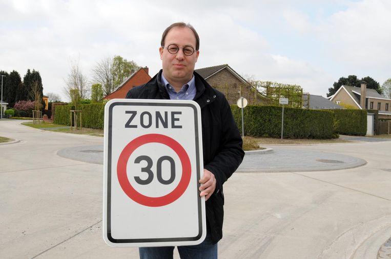 Schepen van Mobiliteit Vincent Laroy met een zone 30-bord in de Bloemetjeswijk.