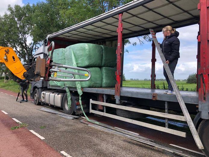 De vrachtwagen wordt volgeladen hooi voor de paarden in Spanje.