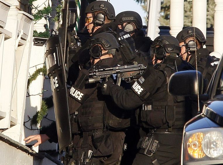 Leden van de arrestatie-eenheid van de Amerikaanse politie plaatsen afluisterapparatuur bij een woning waarvan werd vermoed dat de schutter zich er in schuil hield. Beeld epa