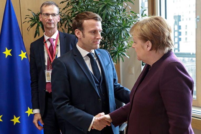 De Duitse bondskanselier Angela Merkel (rechts) en de Franse president Emmanuel Macron begroeten elkaar tijdens de EU-begrotingstop in Brussel. Beeld EPA