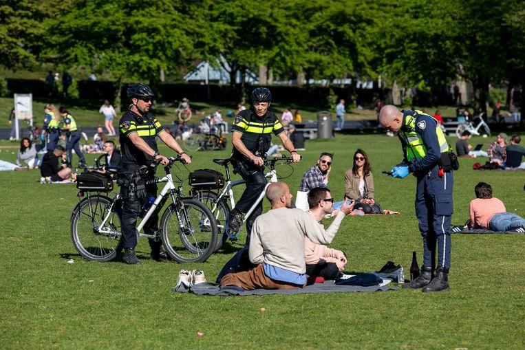 Agenten steunen een handhaver bij een controle in het Westerpark. Beeld Amaury Miller
