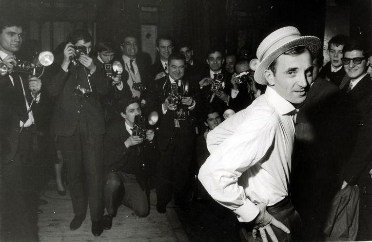 Charles Aznavour poseert met rieten hoedje voor een groep persfotografen ter gelegenheid van zijn eerste one man show in Olympia, Parijs, Frankrijk, 1963. Beeld Hollandse Hoogte / Spaarnestad Photo