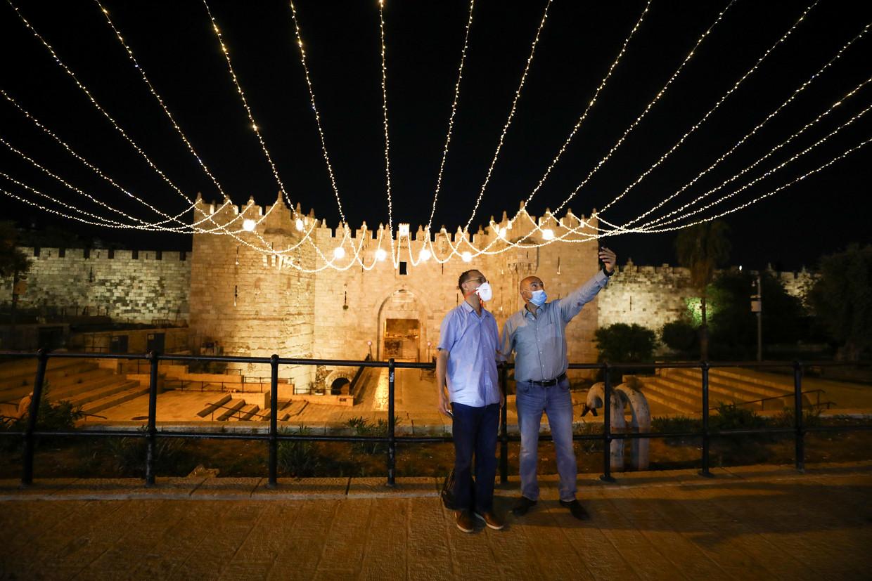Twee mensen nemen een selfie voor de Damascuspoort, versierd voor de heilige maand Ramadan.  Beeld REUTERS