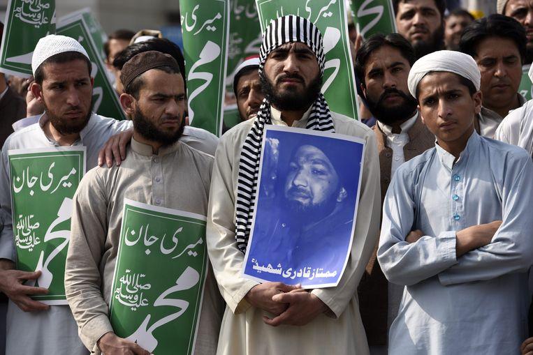 Aanhangers van een Pakistaanse islamitische partij protesteren tegen het doodvonnis voor Mumtaz Qadri, de moordenaar van gouverneur Salman Taseer in 2011. Taseer nam het op voor de christelijke boerenvrouw Asia Bibi, die op grond van de strenge Pakistaanse blasfemiewet in de dodencel belandde, waarin ze al acht jaar verblijft. Dat de gouverneur zich sterk maakte voor haar vonden veel Pakistaanse extremisten eveneens blasfemie.  Beeld EPA