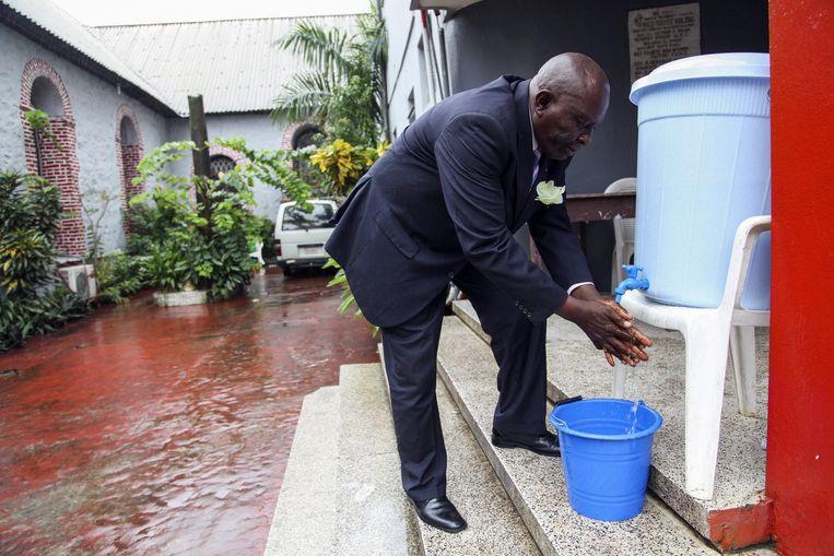 Een man uit Liberia wast zijn handen, ter preventie van ebola. Beeld epa