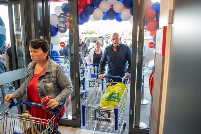 Door een haag van ballonnen betreedt het winkelend publiek, dat in grote getale is gekomen, de vernieuwde Aldi aan de Ootmarsumsestraat in Almelo.