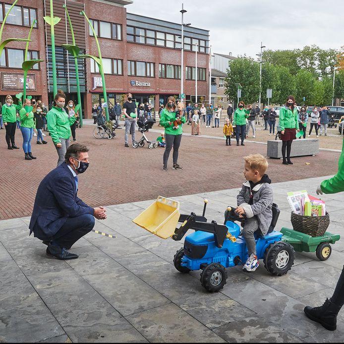 Wethouder Peter van Boekel hurkt bij een kind tijdens de demonstratie vóór De Dierenvriendjes.