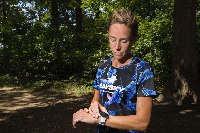 Kim Dillen stelt haar smartwatch in voor een virtual race in het bos.
