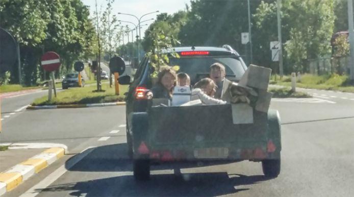 Een vader vervoerde zijn vier kinderen in een aanhangwagen.