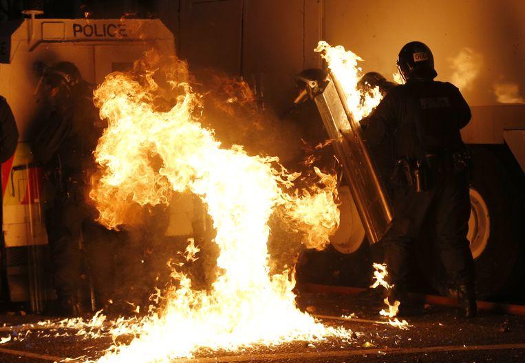 Politie in Belfast wordt zaterdag bestookt met een molotovcocktail. Beeld AP
