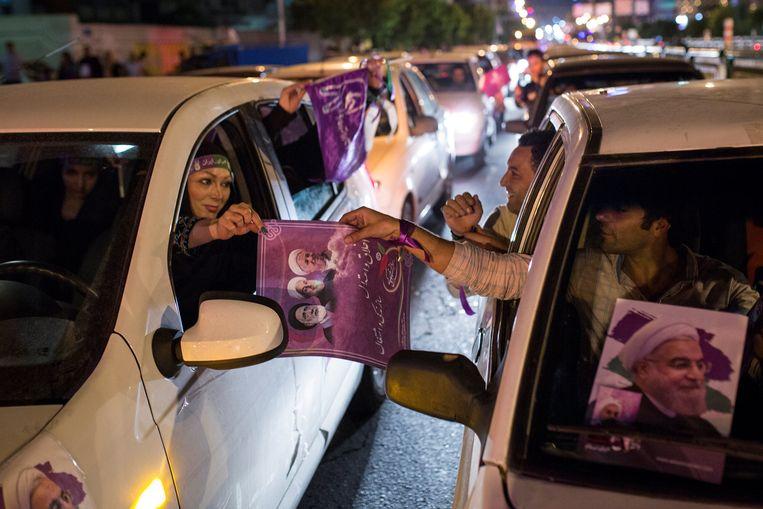 Aanhangers van de zittende president Rohani deelden deze week posters uit tijdens een manifestatie in Teheran. Beeld Reuters