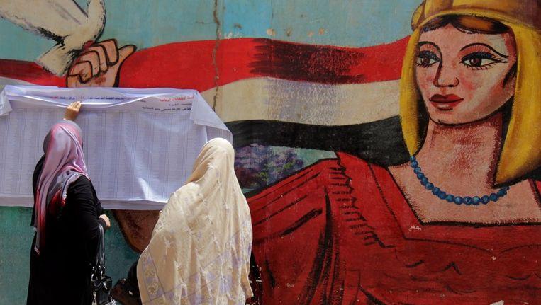 Vrouwen zoeken hun naam op de kiezerslijsten, voordat zij hun stem uitbrengen. Beeld epa