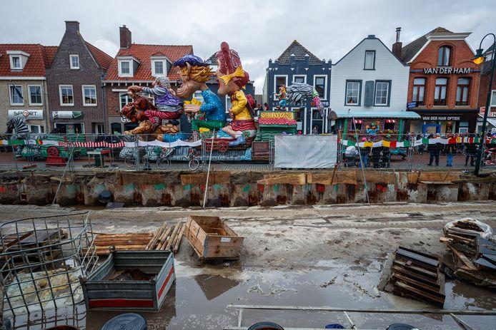 De meterslange carnavalssjaal doet z'n uiterste best de bouwput op te fleuren. Langs de bouwhekken aan de Noordhaven was het af en toe millimeterwerk wagens als deze.