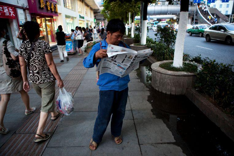 Een krantenlezer in de Chinese stad Guiyang. Beeld Corbis via Getty Images