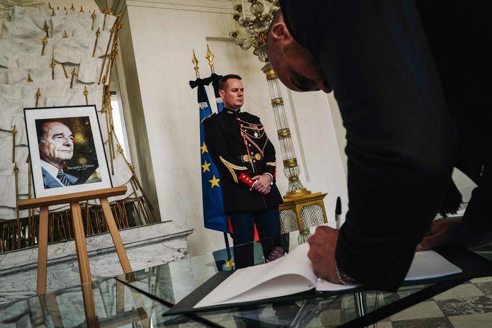 Een man tekent het condoleanceregister voor de Franse president Jacques Chirac.