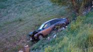 Auto botst met bus en belandt drie meter dieper in weiland