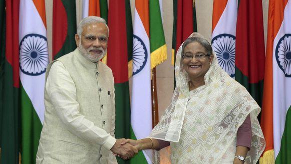 De Indiase premier Narenda Modi en de premier van Bangladesh Sheikh Hasina schudden elkaar de hand.