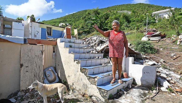 Een vrouw naast haar verwoeste huis op Sint Maarten na orkaan Irma. Beeld null