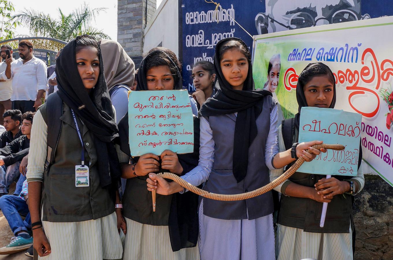 Meisjes demonstreren met een nepslang en protestbordjes.