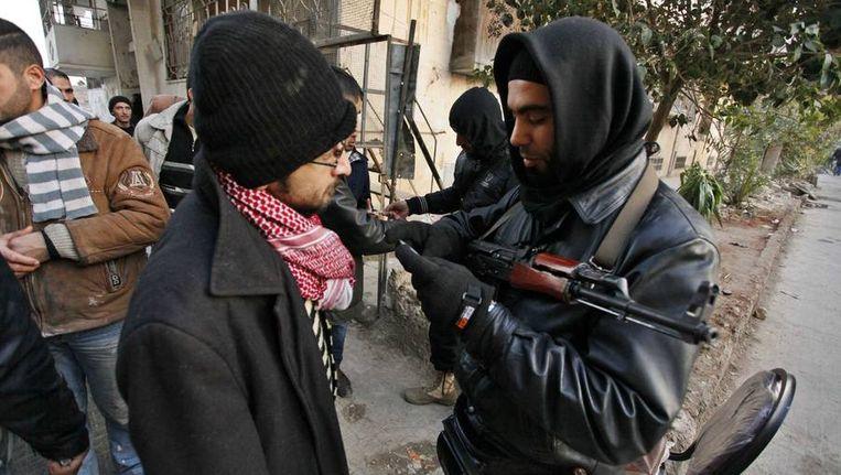 Leden van al-Nusra checken identiteitsbewijzen bij een checkpoint in Aleppo. Beeld reuters