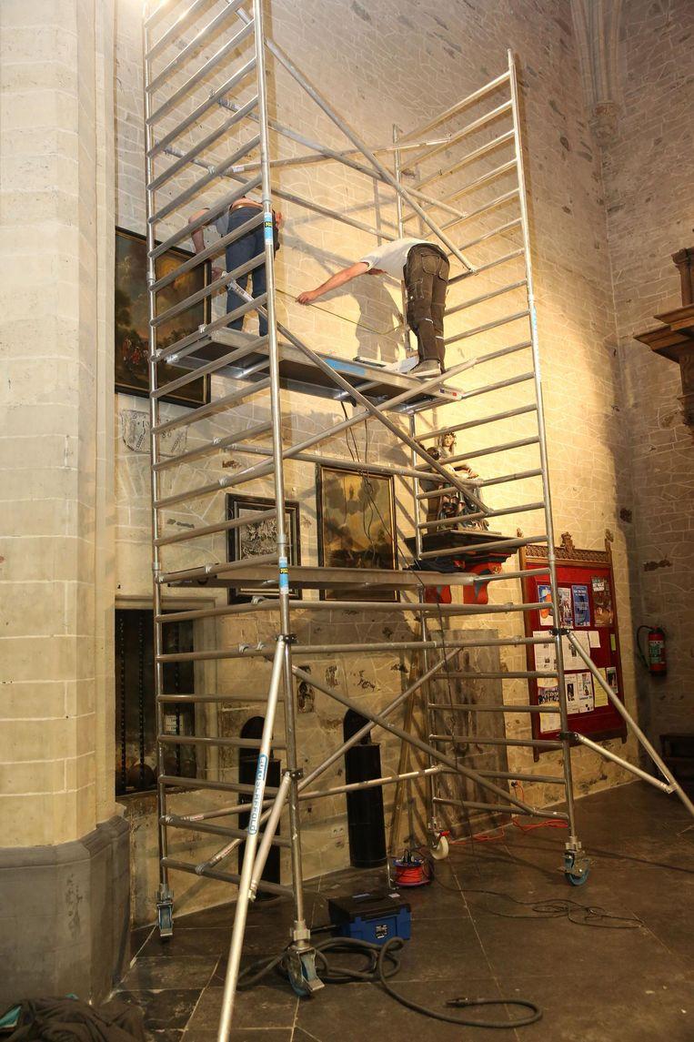Een hele dag was de gespecialiseerde firma in de weer om de schilderijen weer op de torenmuur te hangen.