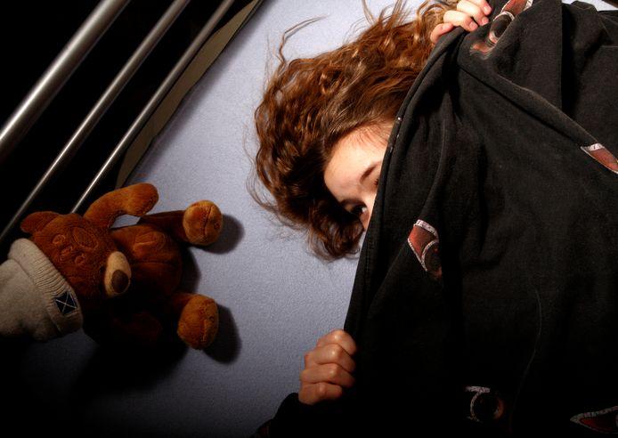 Ter illustratie: Een meisje verstopt zich onder de dekens.