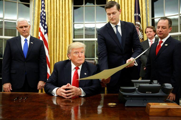 Rob Porter geeft een document door aan president Trump.