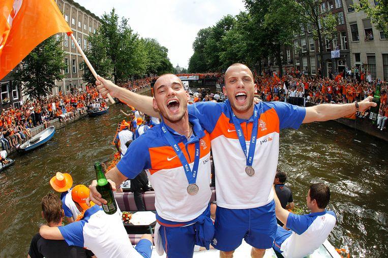 Wesley Sneijder en John Heitinga zwaaien naar het publiek tijdens de rondvaart van het Nederlands elftal door de grachten van Amsterdam. Beeld anp