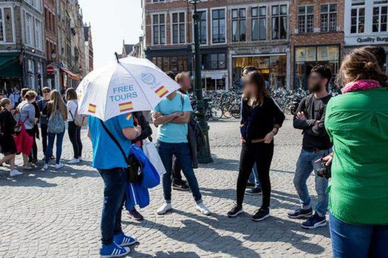 Een man, met paraplu met daarop Free Tours, gidst toeristen.