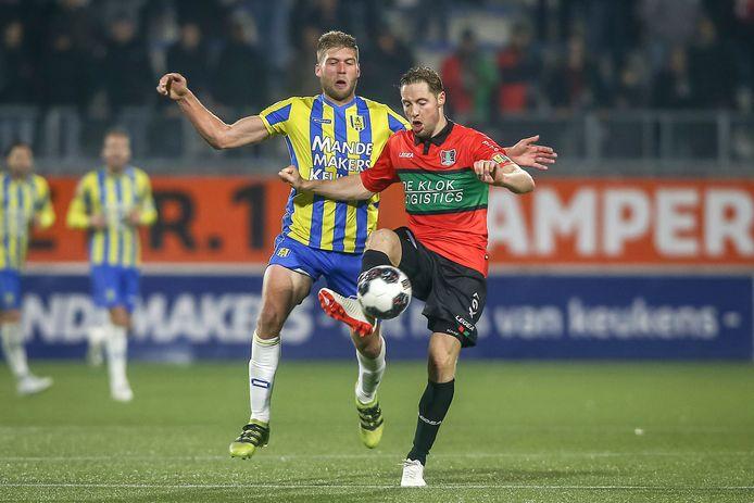 NEC-aanvoerder Rens van Eijden (rechts) in duel met Roland Bergkamp van RKC.