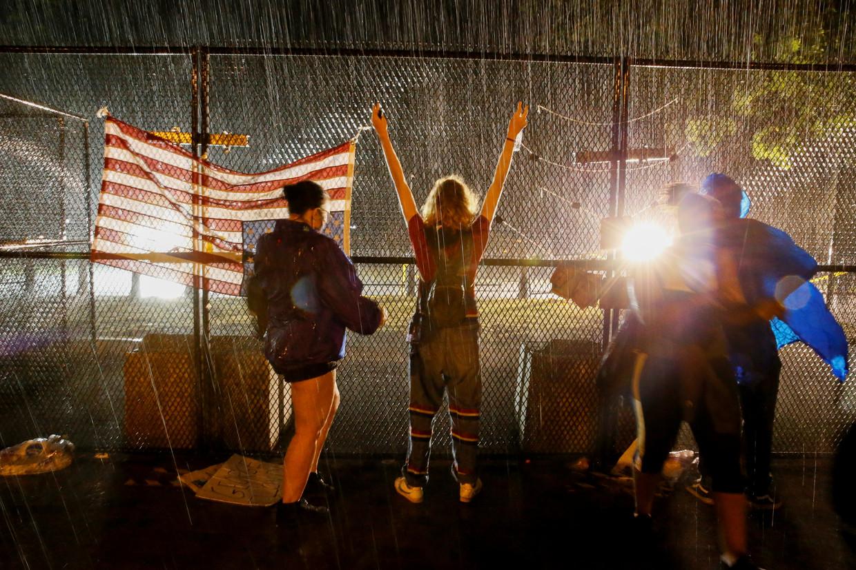 Demonstranten in Washington staan donderdag in de stromende regen achter een hek tegenover het Witte Huis, tijdens een protest na de dood van George Floyd die door de politie van Minneapolis tijdens zijn arrestatie op 25 mei zo werd mishandeld dat hij overleed.