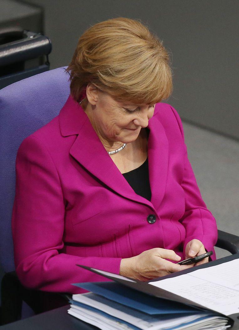 De Duitse bondskanselier Angela Merkel kijkt op haar smartphone. Beeld getty