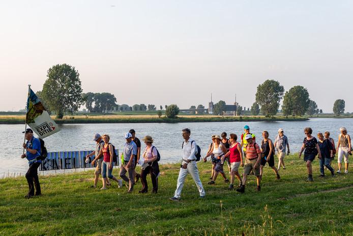 Wandelaars van de Zuiderwaterlinie lopen langs het kunstwerk van Bouke Bruins.