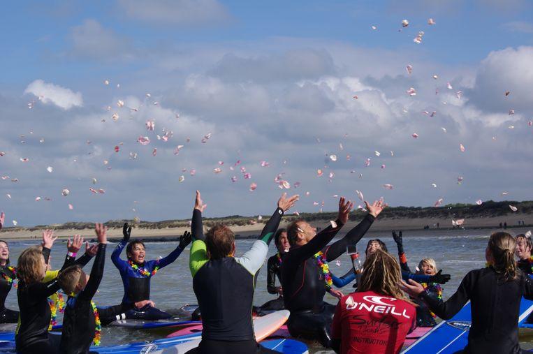De surfers gooien bloemblaadjes de lucht in.