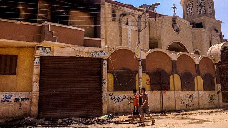 Egyptenaren bij een beschadigde kerk in Caïro, vanmorgen. Beeld afp