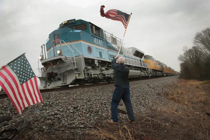 Langs de route zwaait Peter Olyniec met een Amerikaanse vlag als de trein met de kist met daarin het lichaam van de overleden oud-president George H.W. Bush voorbij komt.