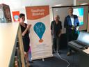 Bieb-directeur Marlie Driessens (l), schrijfster Joke van Leeuwen en wethouder Henri Willems onthulden de banner van het Taalhuis in de Boekelse bieb.