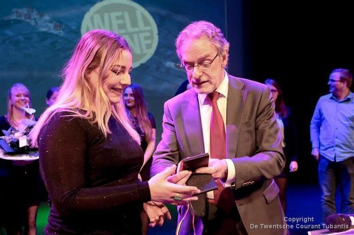 De Vriezenveense Sophie Vugteveen krijgt tijdens het jeugdlintje uit handen van wethouder Jan Binnenmars.