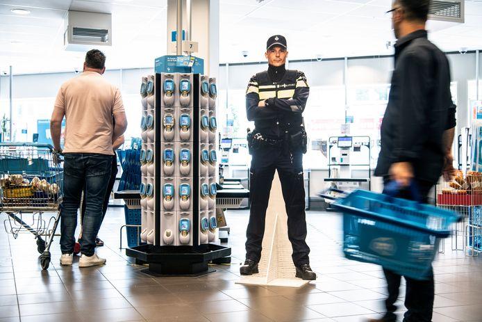 'Kartonnen Koen' waakt over het zelfscanplein bij de Albert Heijn aan de Daalseweg in Nijmegen. Zo hopen politie en supermarkt grootschalige winkeldiefstal tegen te gaan. De wekelijkse schade loopt in de duizenden euro's.